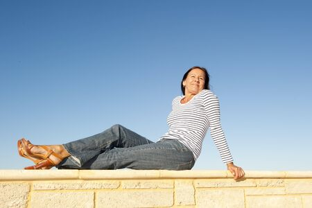Portrait pretty mature woman sitting on a sunny day relaxed and happy on limestone wall, isolated with clear blue sky as background and copy space. photo