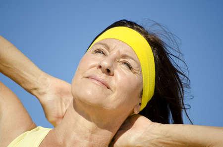 cintillos: Retrato de mujer madura hermosa, alegre, amable, relajado estilo de vida, sano, aislado con el cielo azul como fondo.