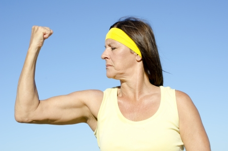 Portrait fit and healthy, confident and determined attractive looking mature woman exercising and strong biceps, isolated with blue sky as background . photo