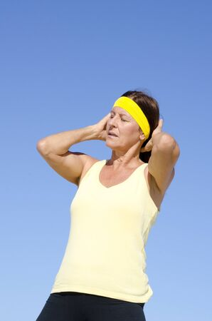 keeping fit: Portrait attractive mature woman, concentrated, exhausted exercising, keeping fit and healthy with active retirement, isolated with blue sky as background and copy space.
