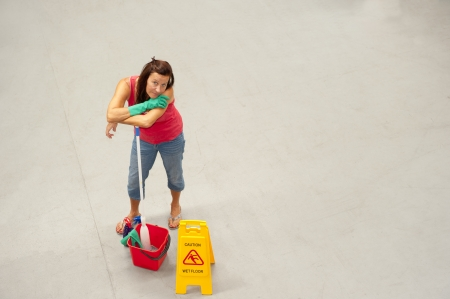 mopped: Overhead portrait of female business cleaner with mob, bucket and Caution Wet Floor Stock Photo