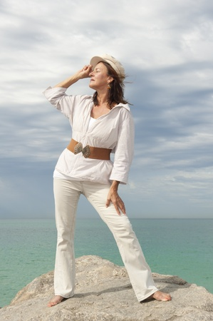aquamarin: Portrait attractive mature woman dressed in white and standing in relaxed and confident pose Stock Photo