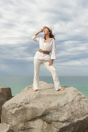 aquamarin: Portrait attractive mature woman dressed in white and standing in relaxed and confident pose on rock at coast Stock Photo