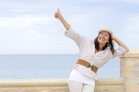 actitud positiva: Retrato feliz mujer atractiva, madura, sonrisa positiva con los pulgares hacia arriba y amistoso, aislado con el océano y cielo nublado como fondo borroso blanco y copia espacio. Foto de archivo