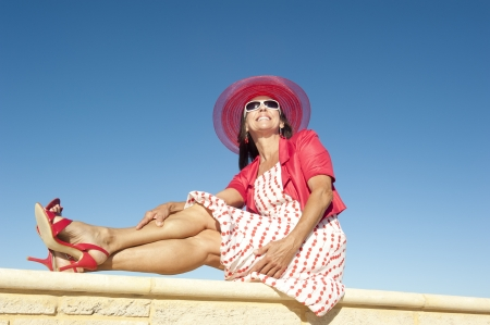 Portrait attractive sexy mature woman dressed in red dress, hat and high heels, sitting relaxed and happy on sunny summer day on wall enjoying active retirement, isolated with blue sky as background and copy space  photo