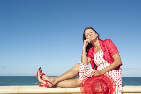 Portrait attractive sexy mature woman dressed in red dress, hat and high heels, sitting relaxed and happy on sunny summer day on wall enjoying active retirement, isolated with ocean and blue sky as background and copy space  photo