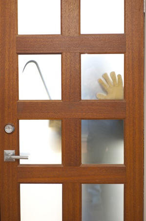 doorlock: Hands of Burglar, thief  with gloves, holding crowbar trying to break in home, unlock door, blurred visible silhouette behind milky windows, with copy space.