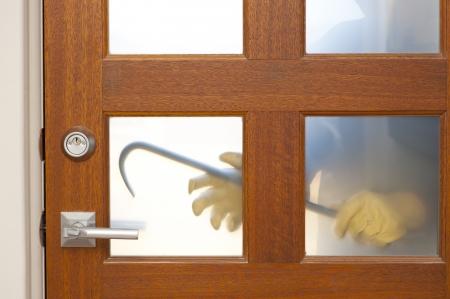 Las manos de ladrón, ladrón con guantes, una palanca que sostiene tratando de entrar en la casa, abrir la puerta, borrosa silueta visible detrás de las ventanas lechoso, con copia espacio. Foto de archivo - 18352629
