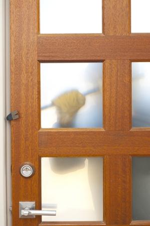 doorlock: Burglar, thief  with gloves, holding crowbar trying to break in home, unlock door, blurred visible silhouette behind milky windows, with copy space.