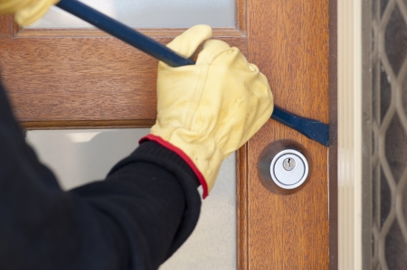 Burglar, thief  with gloves, holding crowbar breaking into home, unlock door, copy space. Stock Photo