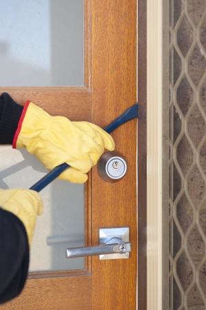 Burglar, thief  with gloves, holding crowbar breaking into home, unlock door, copy space. Stock Photo