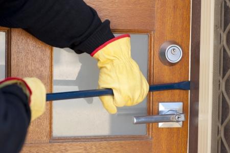 Burglar, thief  with gloves, holding crowbar breaking into home, unlock door, copy space. photo
