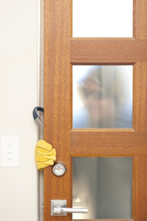 breakin: Burglar, thief  with gloves, holding crowbar breaking into home, unlock door, blurred visible silhouette behind milky windows, with copy space. Stock Photo