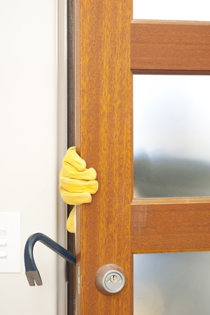 doorlock: Burglar, thief  with gloves, holding crowbar breaking into home, unlock door, blurred visible silhouette behind milky windows, with copy space. Stock Photo