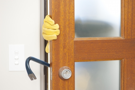 doorlock: Burglar, thief  with gloves, holding crowbar breaking into home, unlock door, blurred visible silhouette behind milky windows, with copy space. Stock Photo