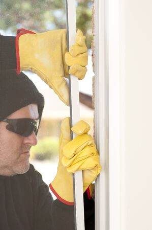 Male thief with black hood, gloves and sunglasses trying to break in residential house, home,  through window, with copy space. photo