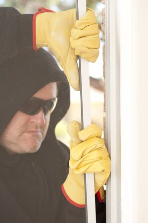 Male burglar with black hood, gloves and sunglasses trying to break in residential house, home,  through window, with copy space. photo