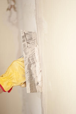 Closeup of palette-knife or scraper and cement filling for house renovation construction in hands of handyman and worker fixing interior wall, with blurred background and copy space. Stock Photo - 18457926