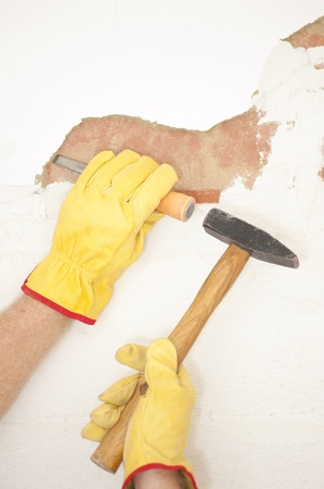 Workers hands with yellow gloves repairing, renovating interior wall in house with hammer and bite or chisel or gouge. photo