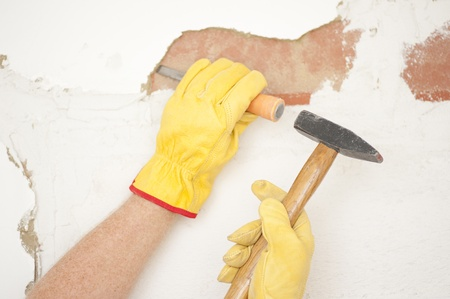 gouge: Workers hands with yellow gloves repairing, renovating interior wall in house with hammer and bite or chisel or gouge.