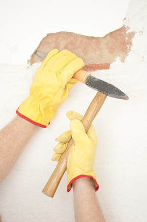 Workers hands with yellow gloves repairing, renovating interior wall in house with hammer and bite or chisel or gouge.