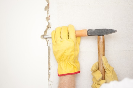 Workers hands with yellow gloves repairing, renovating interior wall in house with hammer and bite or chisel or gouge. Stock Photo - 18457932