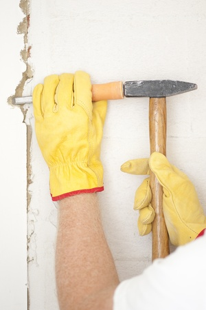Workers hands with yellow gloves repairing, renovating interior wall in house with hammer and bite or chisel or gouge. Stock Photo - 18457931