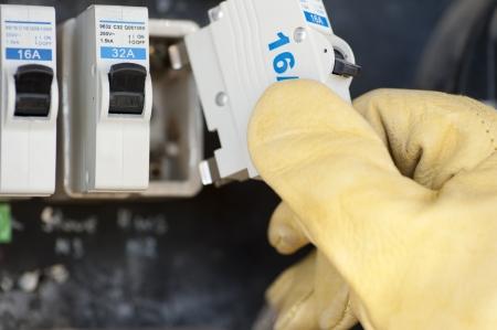 contador electrico: La mano con la protecci�n de guantes de electricista en el medidor el�ctrico o placa de interruptores de fusibles de su hogar en el intercambio. Foto de archivo