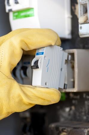 meter box: La mano con la protecci�n de guantes de electricista en el medidor el�ctrico o placa de interruptores de fusibles de su hogar en el intercambio. Foto de archivo