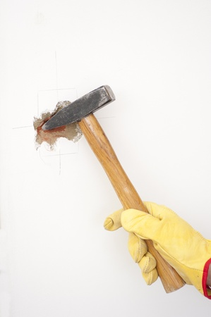 damaging: Hammer in hand with gloves of man smashing hole in white home brick wall, demolishing, damaging house room, isolated with white background and copy space.