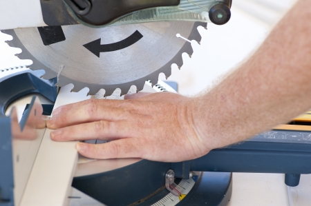 Closeup of sharp circular saw blade and hand of carpenter or worker, concept image safety and security at workplace.