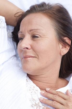 Ritratto rilassato attraente donna matura riposo a letto con il sorriso sul volto, sereno, felice espressione, godendo di stile di vita per il tempo libero. Archivio Fotografico