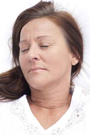 donne mature sexy: Ritratto rilassato attraente donna matura riposo a letto con il sorriso sul volto, sereno, felice espressione, godendo di stile di vita per il tempo libero. Archivio Fotografico