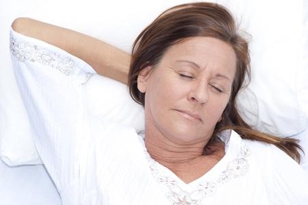 donne mature sexy: Ritratto rilassato donna matura attraente addormentato, riposo a letto con gli occhi chiusi e sorriso sul viso, sereno, felice espressione, godendo di stile di vita per il tempo libero.