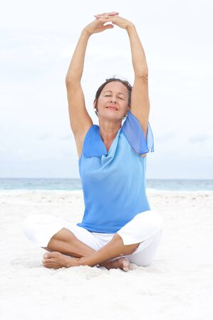 Portrait Beautiful mature woman sitting peaceful and happy with arms up at beach, wearing blue blouse, with ocean and white overcast sky as blurred background and copy space. photo