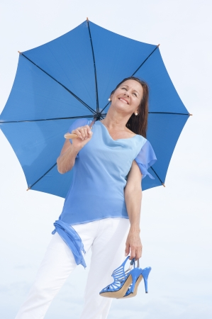 Portrait beautiful looking mature woman with blue umbrella and high heel sandals in hand standing relaxed and happy smiling isolated outdoor, with bright white sky as background and copy space. photo