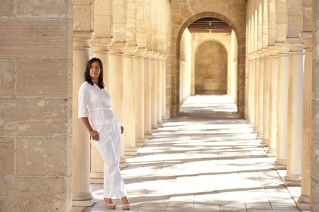 Portrait confident attractive mature woman standing relaxed, dressed in white and high heel shoes in historic stone archway at sunny day photo