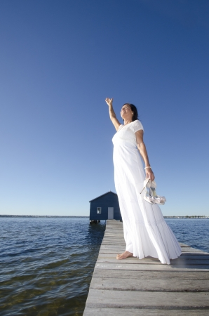 Portrait attractive mature woman standing in white long wedding dress joyful with high heels on wooden boardwalk at sea photo