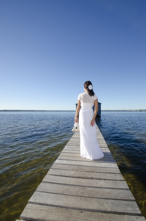 Portrait attractive mature woman standing in white long wedding dress relaxed  with high heels on wooden boardwalk at sea, with coastline horizon and blue sky as background and copy space. photo