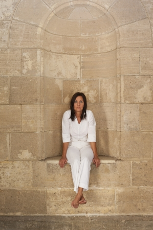 Portrait attractive mature woman sitting alone, lonely and with sad facial expression in alcove at big brick wall  photo