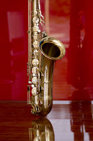 Shiny golden shimmering saxophone on polished wooden floor, isolated with red background and optical reflection  photo