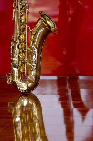 wind instrument: Shiny golden shimmering saxophone on polished wooden floor, isolated with red background and optical reflection  Stock Photo