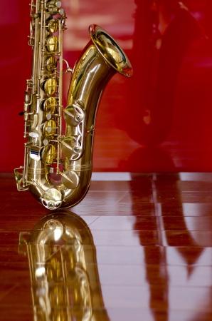 Shiny sassofono luccicante d'oro sul lucido pavimento di legno, isolato con sfondo rosso e la riflessione ottica
