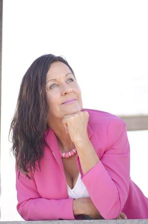 Ritratto sexy donna matura con fiducioso e felice sorriso, pensieroso contemplando, indossando elegante giacca rosa, isolato su bianco e con sfondo sfocato