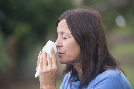 hayfever: Portrait beautiful mature woman suffering from cold or flu infection, sneezing into tissue, painful seasonal hayfever, with blurred outdoor background and copy space.