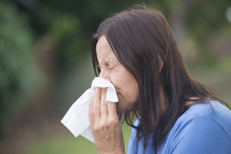 Portrait attractive mature woman suffering from cold or flu infection, sneezing into tissue, painful seasonal hayfever, with blurred outdoor background and copy space. Stock Photo