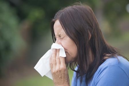 Ritratto donna matura attraente affetti da infezione da raffreddore o influenza, starnuti in tessuto, febbre da fieno doloroso stagionale, con sfondo sfocato all'aperto e spazio di copia.