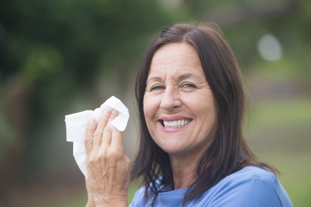 allergic reaction: Portrait smiling attractive mature woman suffering from cold or flu infection, sneezing into tissue, painful seasonal hayfever, with blurred outdoor background and copy space.