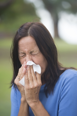 Portrait attractive mature woman suffering from cold or flu infection, sneezing into tissue, painful seasonal hayfever, with blurred outdoor background and copy space. photo