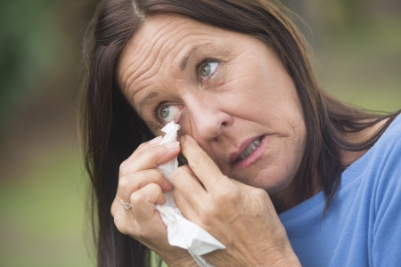 whining: Portrait attractive sad mature woman cleaning eye with tissue, in tears or crying, with blurred outdoor background. Stock Photo